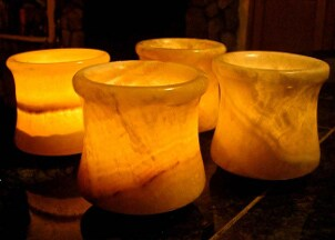 Collection of lighted Egyptian alabaster candle holders in a dark room
