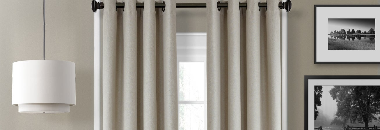 A pair of window treatments hanging over a window
