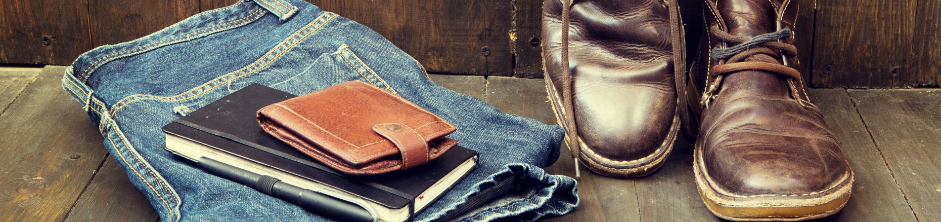 Brown leather boots next to jeans and a wallet