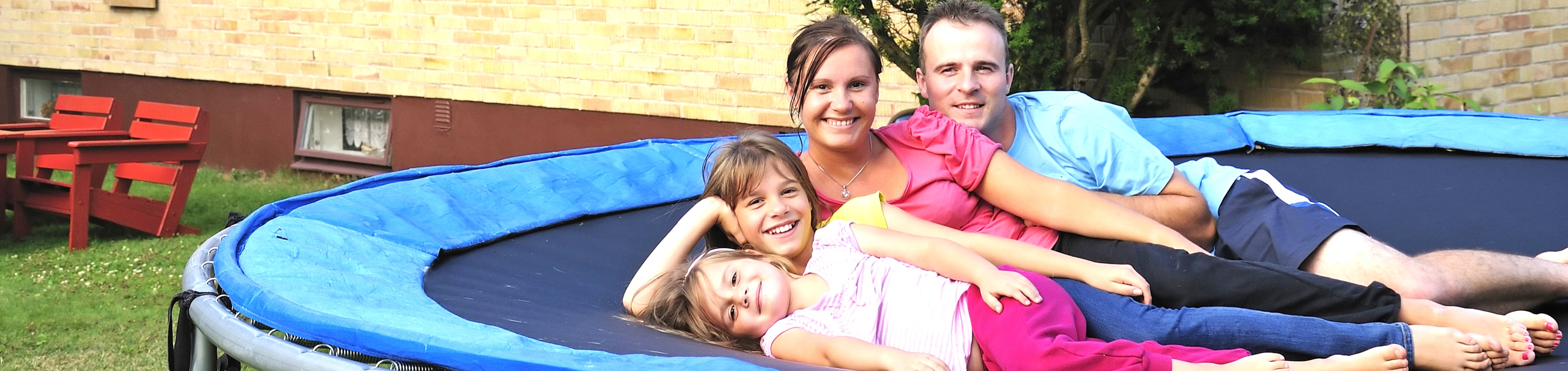 Family smiling on an outdoor trampoline