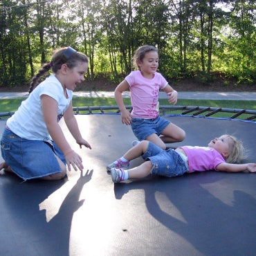 Three young girls playing on a trampoline