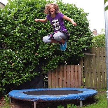 Girl jumping on a small, outdoor trampoline