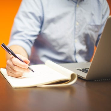 Man using laptop computer and taking notes