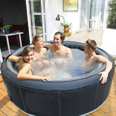 Four young people hanging out in a hot tub