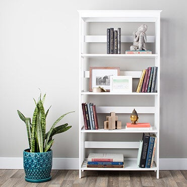 White bookcase with accents, books, and shelf decor