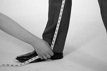Man in dress clothes having his inseam measured