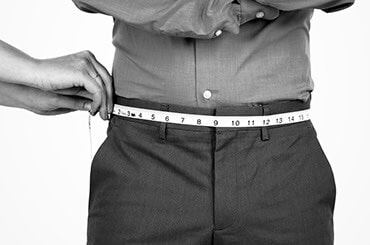 Man in dress clothes having his waist measured