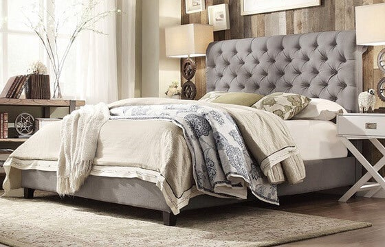 Grey Upholstered Bed With Layers Of Bedding