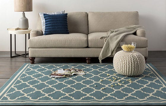 Sofa with blue trellis rug and cream pouf