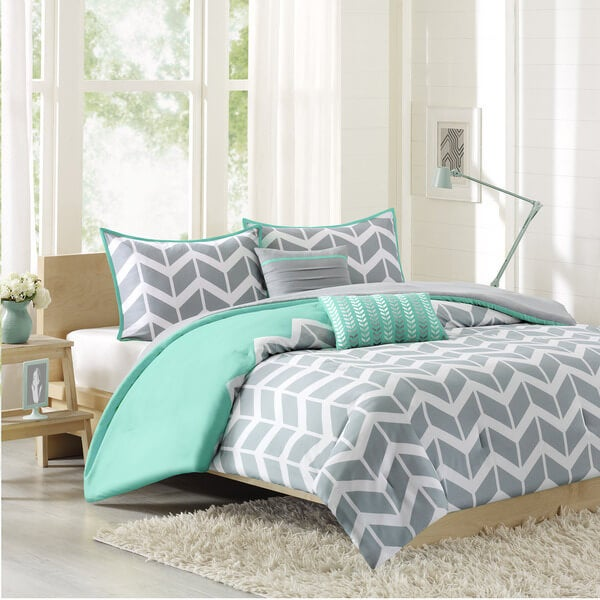 bed made with gray and white chevron comforter set with teal accents