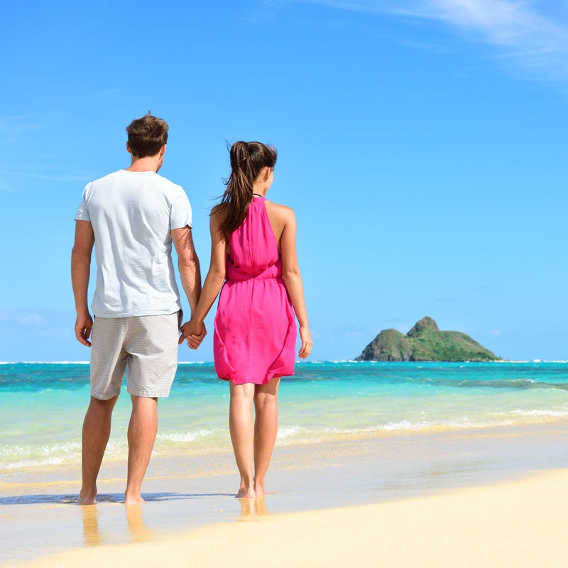 man in white t-shirt and woman in pink dress walk on the beach