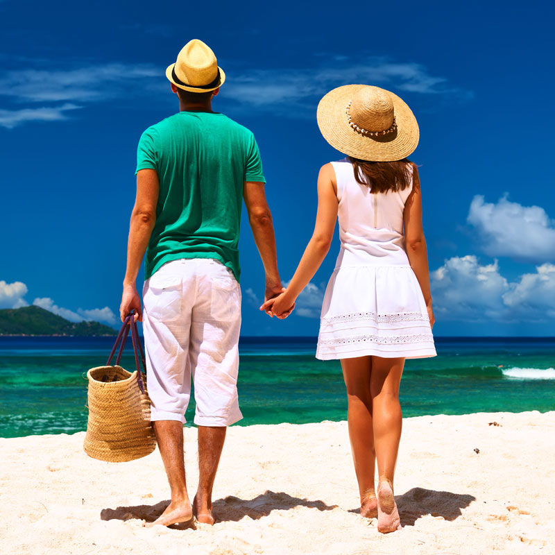 man in green shirt and woman in white dress walk on the beach