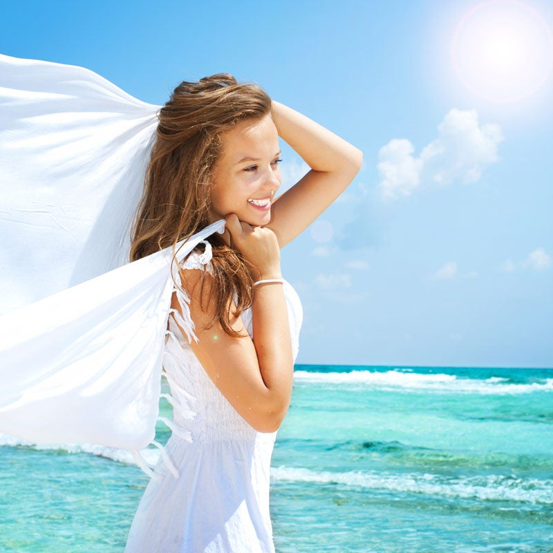 woman in white dress with scarf on the beach