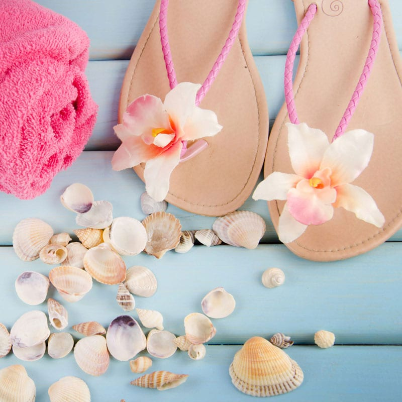 leather flip flops sitting on a blue deck with a towel and seashells