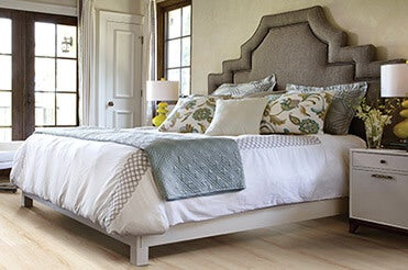 Upholstered headboard bed with wood-look laminate flooring