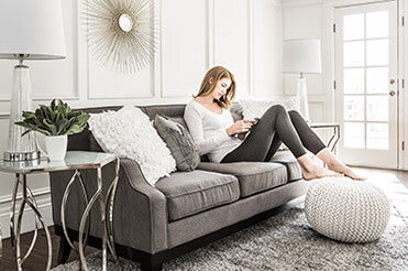 Woman sitting on gray couch reading