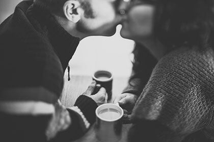 Black and white picture of two people kissing while holding coffee mugs