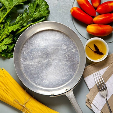 Empty aluminum skillet on countertop surrounded by fresh vegetables