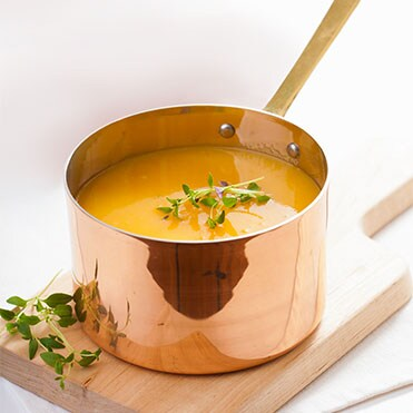 Copper sauce pan filled with pumpkin soup, sitting on a cutting board