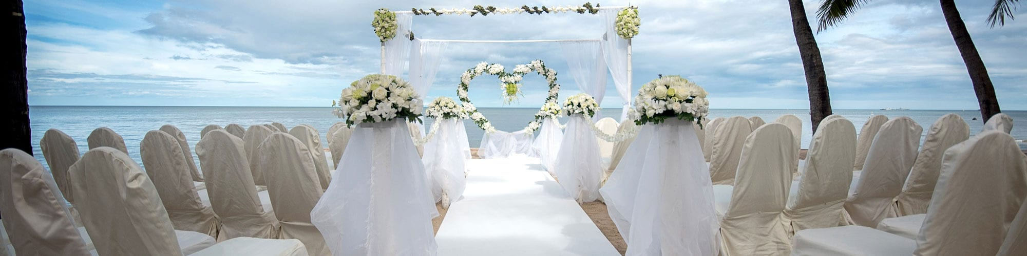wedding ceremony aisle on the beach with chairs on either side