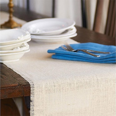 Cream burlap table runner with blue napkins on brown table, set with plates