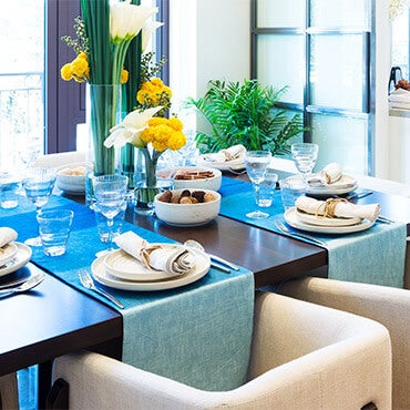 Dining room table set with two blue table runners, tableware, and centerpiece