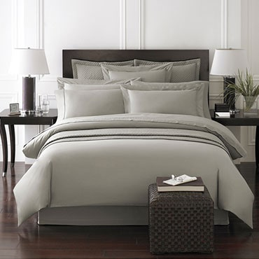 Gray bedding on a dark wood bed frame