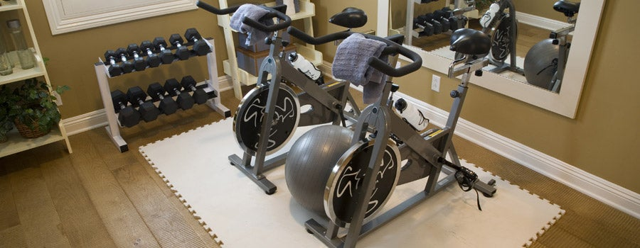 Home gym with stationary bikes, weights, and water in the room