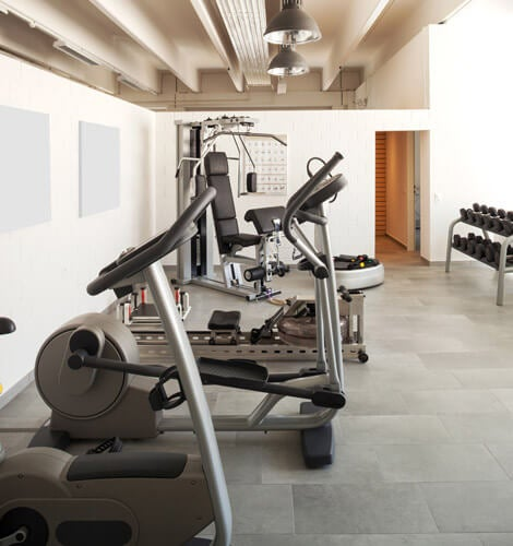 Three home gyms with equipment, wall of mirrors, and TV's mounted on the wall