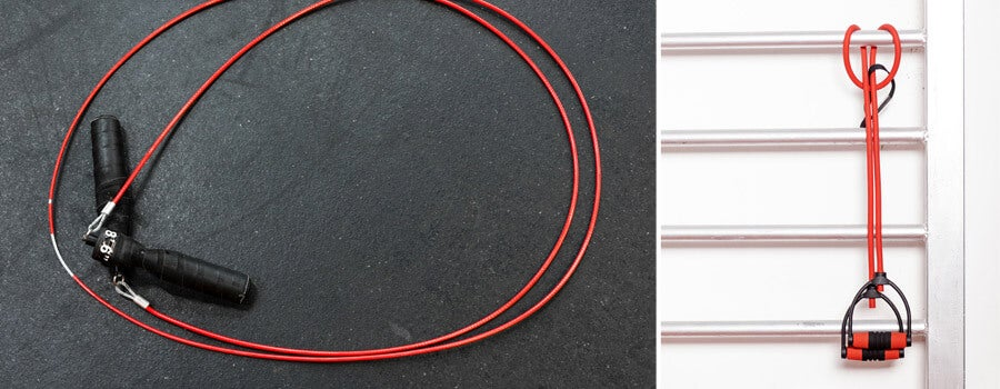 Red jump rope on black gym floor, and a red resistance band hangin on wall