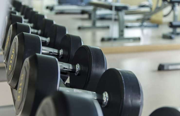 Set of weights in a gym setting, and a kettlebell, weighted medicine ball, and red dumbbells
