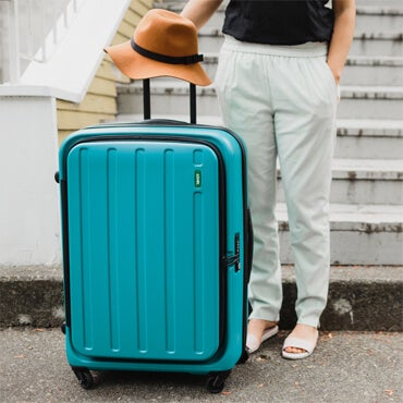 Woman standing next to large teal blue suitcase