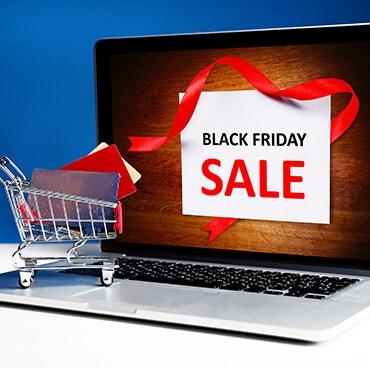 Black Friday sale shown on laptop screen, with a small grocery cart filled with credit cards and gift cards