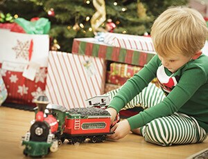 Little boy on Christmas morning playing with a train by the Christmas tree