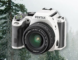 A black and white Pentax digital camera with snowy Christmas trees in the background