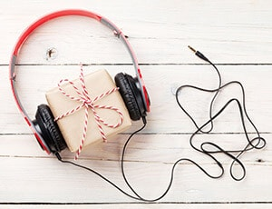 Set of red headphones wrapped around a Christmas present