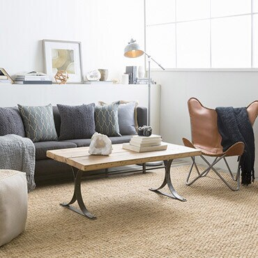 Jute rug in living room with a sofa, chair, coffee table, and pouf