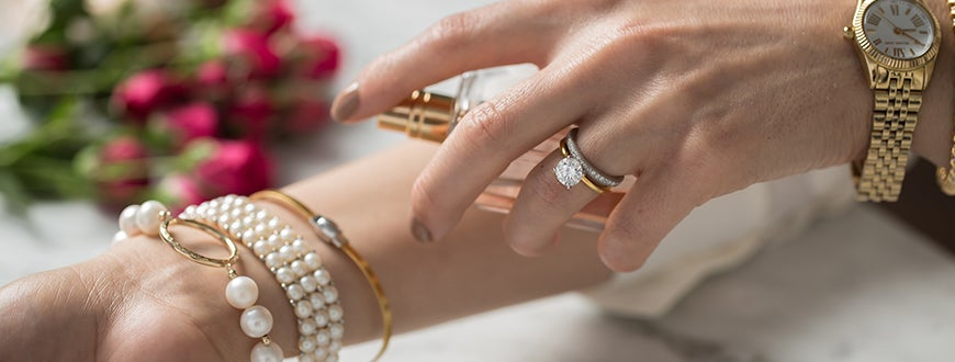 Woman spraying perfume on her wrist wearing a diamond ring