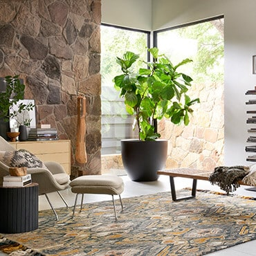 Mid-century modern living room with a close up on chair and hand knotted wool rug in grey and brown