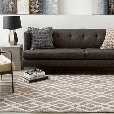 Grey and white geometric patterned hand tufted rug in living room shown with sofa, accent chair, and side table