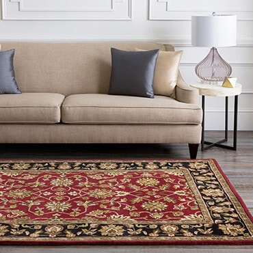 Traditional wool rug in red, black, and beige. Shown with sofa, side table, and table lamp