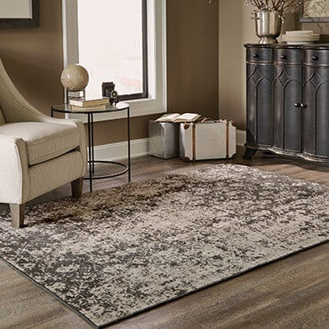 Distressed grey and black area rug with accent tables, chair, and decorative accessories
