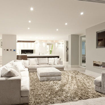 Modern carpeted living room shown with sectional, love seat, and an area rug
