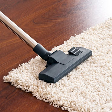 Close up of a vacuum cleaning a rug