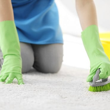 Close up of a woman cleaning a rug using a spounge and wearing rubber gloves