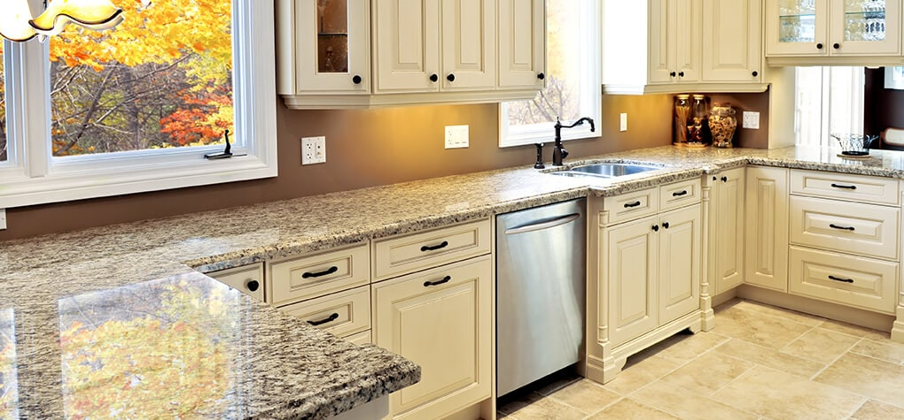 Light kitchen with off white cabinets and light granite countertops shown with stainless steel dishwasher.