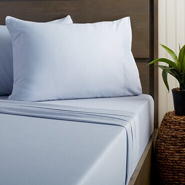 A bed with blue statin 300 thread count sheets on it