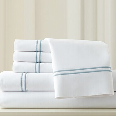 A stack of white 1000 thread count cotton blend sheets with blue hem stitching