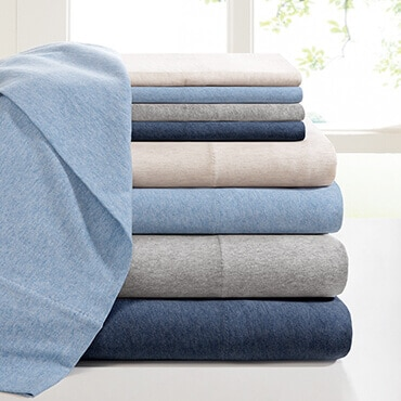 A stack of blue and gray jersey knit sheet set