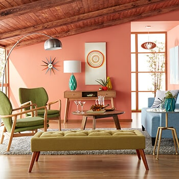 Mid century modern living room with pink walls and green chairs